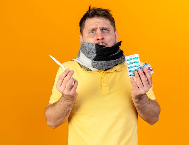 Verwirrter junger blonder kranker slawischer mann, der mund mit schal bedeckt