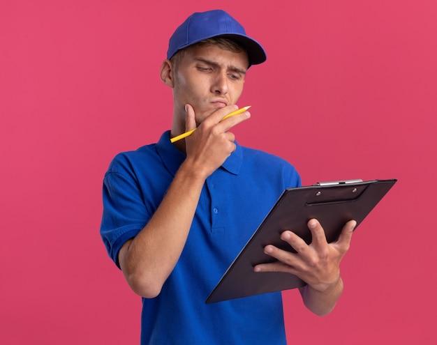 Verwirrter junger blonder lieferjunge legt hand auf kinn, das bleistift hält und schaut auf zwischenablage auf rosa