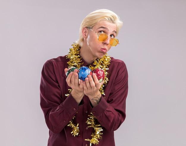 Verwirrter junger blonder mann mit brille mit lametta-girlande um den hals, der weihnachtskugeln hält, die nach oben schürzen lippen einzeln auf weißem hintergrund mit kopienraum suchen