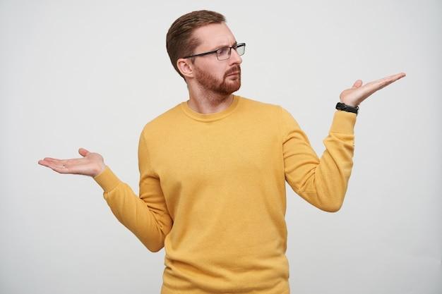 Verwirrter junger brünetter bärtiger mann in brille, der die augenbrauen runzelte und auf seine erhobene handfläche schaute, während er posierte, freizeitkleidung und armbanduhr trug