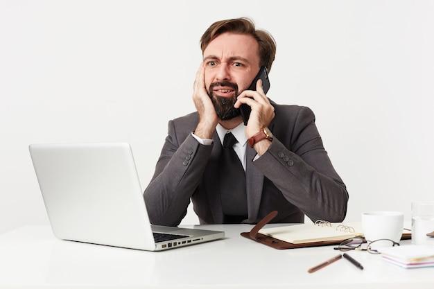Verwirrter junger brünetter mann mit bart, der formelle kleidung trägt, während er über weiße wand arbeitet, kopf auf erhobene hand lehnt und verwirrt auf dem bildschirm seines laptops schaut