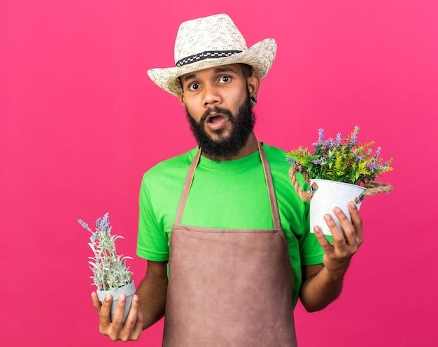 Verwirrter junger gärtner afroamerikanischer typ mit gartenhut, der blumen im blumentopf hält