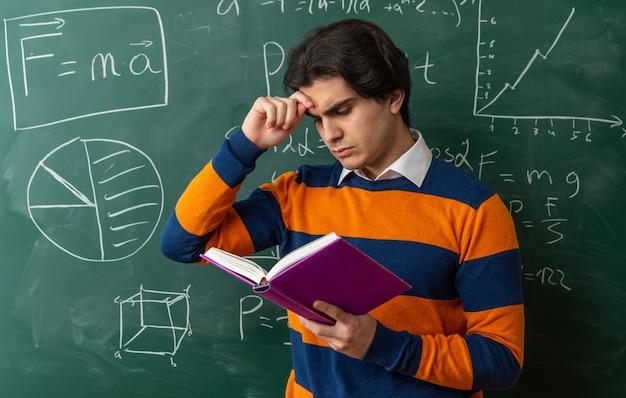 Verwirrter junger geometrielehrer, der vor der tafel im klassenzimmer steht und die stirn berührt, liest buch