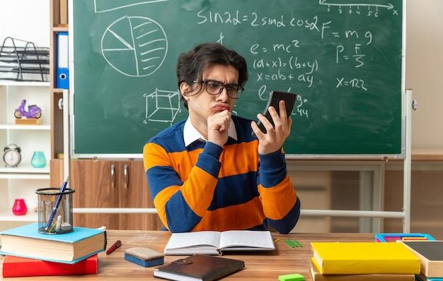 Verwirrter junger geometrielehrer mit brille, der am schreibtisch mit schulmaterial im klassenzimmer sitzt und die hand am kinn hält und den taschenrechner ansieht