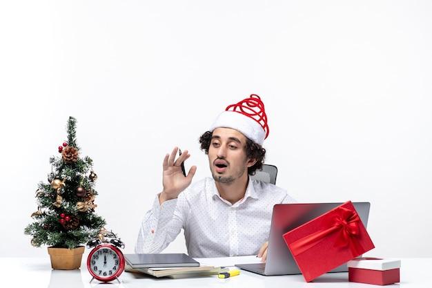 Verwirrter junger geschäftsmann mit lustigem weihnachtsmannhut, der das schreiben von notizen prüft und weihnachten im büro auf weißem hintergrund feiert