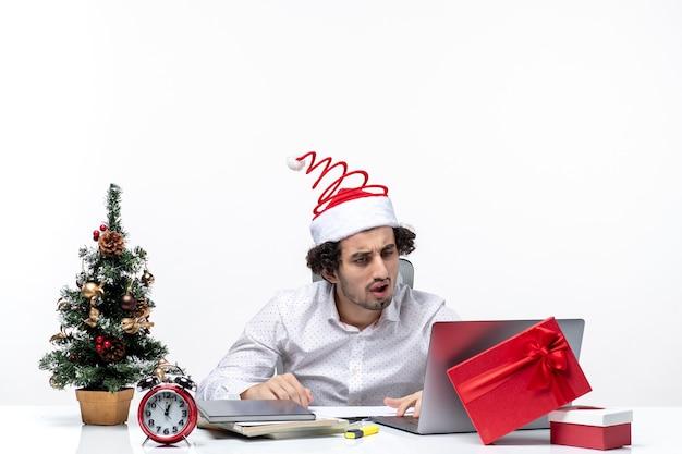 Verwirrter junger geschäftsmann mit lustigem weihnachtsmannhut, der seine mails auf laptop im büro auf weißem hintergrund prüft