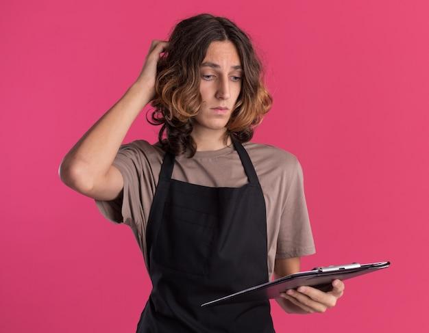 Verwirrter junger gutaussehender friseur, der uniform hält und die zwischenablage anschaut, die den kopf isoliert auf rosa wand berührt
