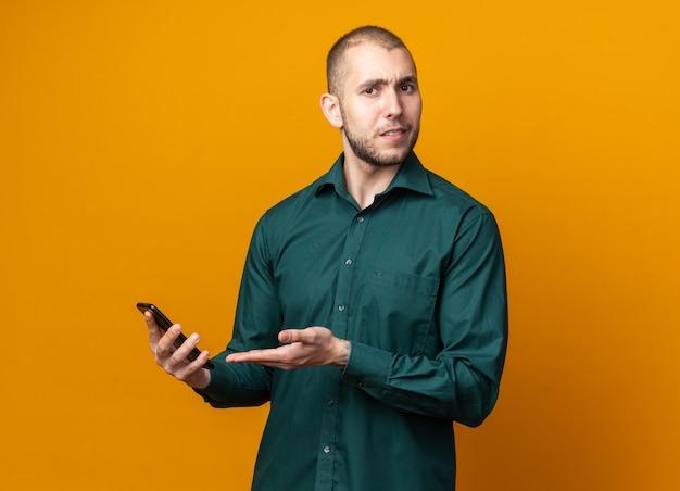 Verwirrter junger gutaussehender kerl, der grünes hemd hält und mit der hand auf das telefon zeigt