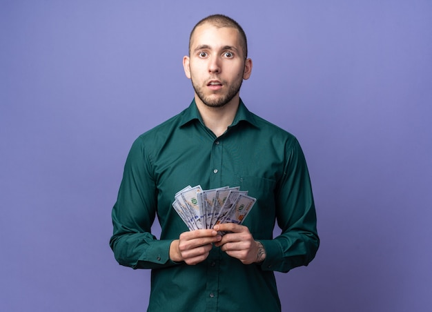 Verwirrter junger gutaussehender kerl, der grünes hemd mit bargeld trägt