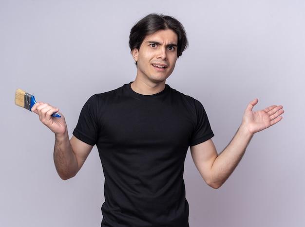 Verwirrter junger gutaussehender kerl, der schwarzes t-shirt hält, das pinsel spreizt, die hand lokalisiert auf weißer wand verbreitet