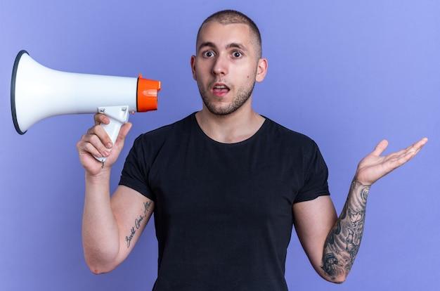 Verwirrter junger gutaussehender kerl mit schwarzem t-shirt mit lautsprecher auf blauem hintergrund