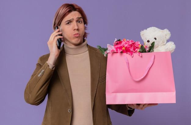 Verwirrter junger gutaussehender mann, der am telefon spricht und eine rosa geschenktüte mit blumen und teddybär hält