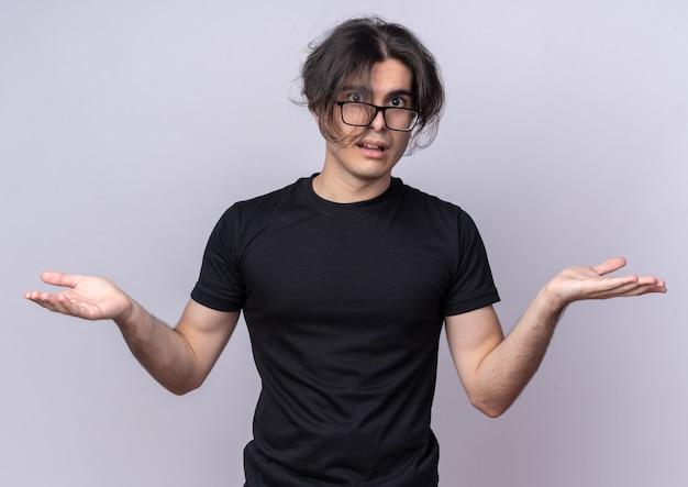 Verwirrter junger gutaussehender mann, der schwarzes t-shirt und brille trägt, die hände lokalisiert auf weißer wand verbreiten