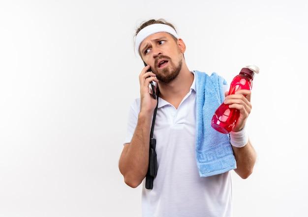 Verwirrter junger, gutaussehender, sportlicher mann mit stirnband und armbändern, der am telefon spricht und eine wasserflasche mit springseil und handtuch auf den schultern hält, isoliert auf weißer wand mit kopierraum