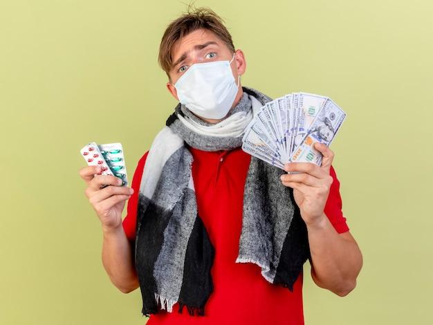 Verwirrter junger hübscher blonder kranker mann, der maske hält, die geld und packungen der medizinischen pillen hält, die front lokal auf olivgrüner wand betrachten