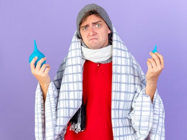 Verwirrter junger hübscher blonder kranker mann, der wintermütze und schal trägt, die in plaid eingewickelt sind, das einläufe hält, die auf lila wand lokalisiert werden
