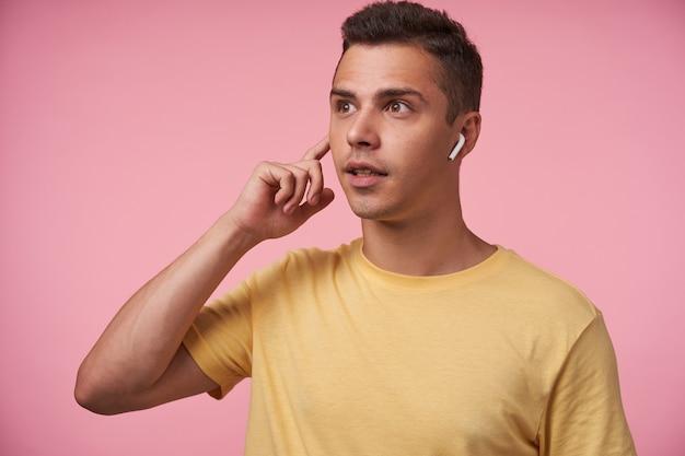 Verwirrter junger hübscher braunäugiger brünetter kerl gekleidet in gelbem t-shirt, das erhobenen zeigefinger auf ohrhörer hält, während er überraschend nach vorne schaut, isoliert über rosa hintergrund