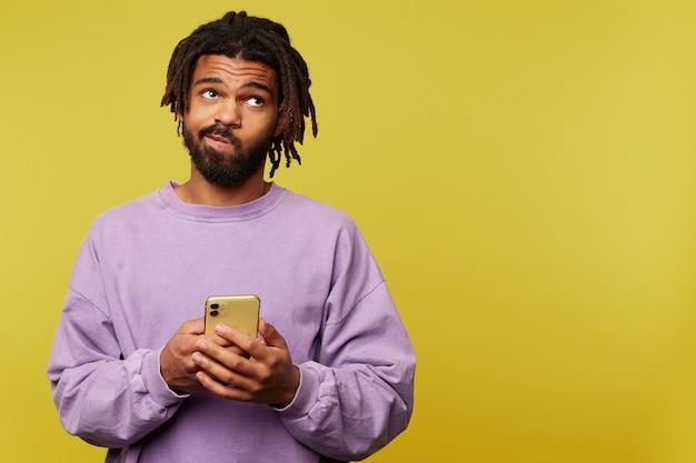 Verwirrter junger hübscher brünetter bärtiger mann mit dunkler haut, die seinen mund verdreht, während er nachdenklich nach oben schaut und über gelbem hintergrund mit smartphone steht