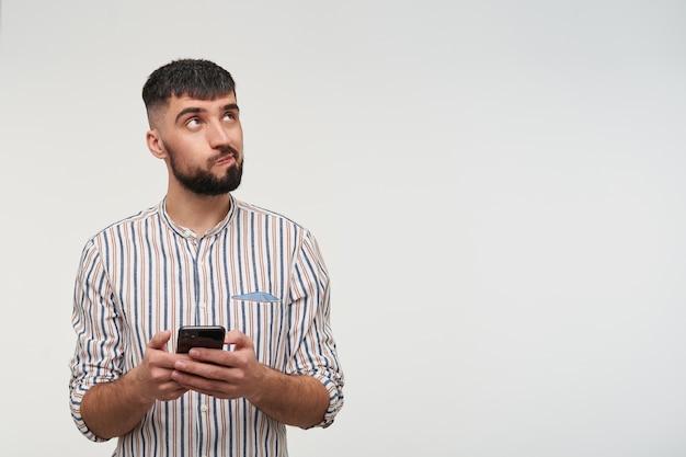 Verwirrter junger hübscher brünetter mann mit bart, der nachdenklich nach oben schaut und seinen mund dreht, handy in erhobenen händen hält, während er über weißer wand posiert