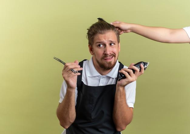 Verwirrter junger hübscher friseur, der schere und haarschneidemaschine hält, die seite mit jemandem betrachtet, der sein haar kämmt, das auf olivgrün mit kopierraum isoliert wird