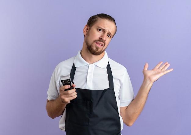Verwirrter junger hübscher friseur, der uniform hält, die haarschneidemaschinen hält und leere hand zeigt, die auf purpur mit kopienraum isoliert wird
