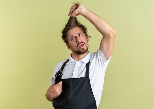 Verwirrter junger hübscher friseur, der zur seite schaut, die sein eigenes haar zieht, das haarschneidemaschinen isoliert auf olivgrün mit kopienraum hält