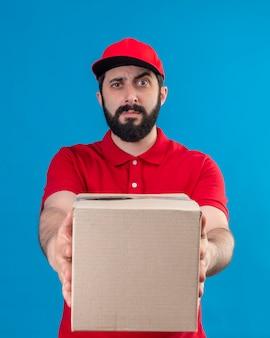 Verwirrter junger hübscher kaukasischer lieferbote, der rote uniform und kappe trägt, die karton in richtung kamera streckt, die auf blau lokalisiert wird