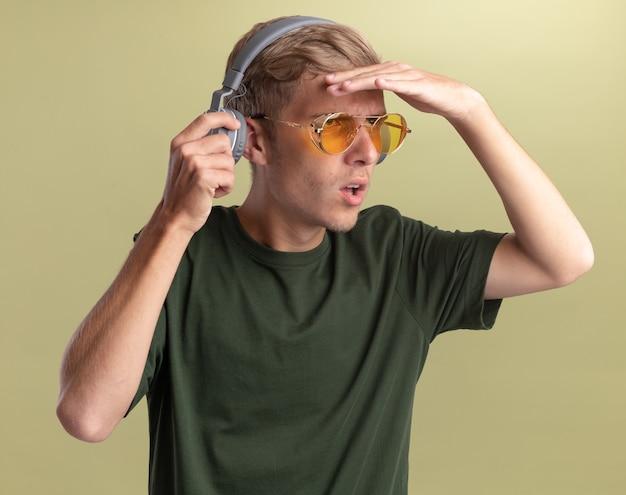 Verwirrter junger hübscher kerl, der grünes hemd mit brille und kopfhörern trägt, die entfernung mit hand lokalisiert auf olivgrüner wand betrachten