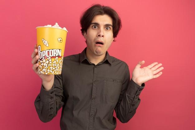 Verwirrter junger hübscher kerl, der schwarzes t-shirt hält, das eimer popcorn spreizende hand lokalisiert auf rosa wand hält