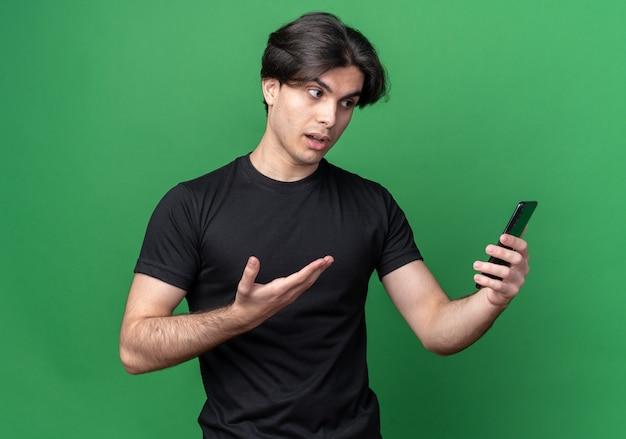 Verwirrter junger hübscher kerl, der schwarzes t-shirt hält und punkte mit hand am telefon lokalisiert auf grüner wand trägt