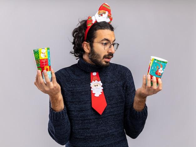Verwirrter junger hübscher kerl, der weihnachtskrawatte mit haarreifen hält und weihnachtsbecher lokalisiert auf weißem hintergrund hält