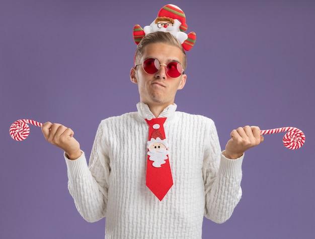Verwirrter junger hübscher kerl, der weihnachtsmann-stirnband und krawatte mit gläsern hält, die weihnachts-zuckerstangen halten, die seite lokalisiert auf lila hintergrund betrachten