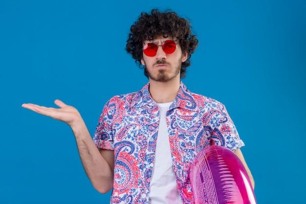 Verwirrter junger hübscher lockiger mann, der sonnenbrille hält, die schwimmring zeigt, der leere hand auf lokalisiertem blauem raum zeigt
