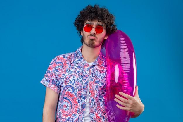 Verwirrter junger hübscher lockiger mann, der sonnenbrillen hält, die schwimmring halten, die linke seite auf lokalisiertem blauem raum betrachten