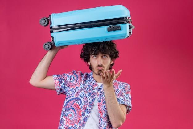 Verwirrter junger hübscher lockiger reisender mann, der koffer auf kopf setzt und leere hand auf isoliertem rosa raum mit kopienraum zeigt