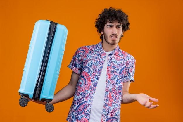 Verwirrter junger hübscher lockiger reisender mann, der koffer hält und leere hand auf lokalisiertem orange raum zeigt
