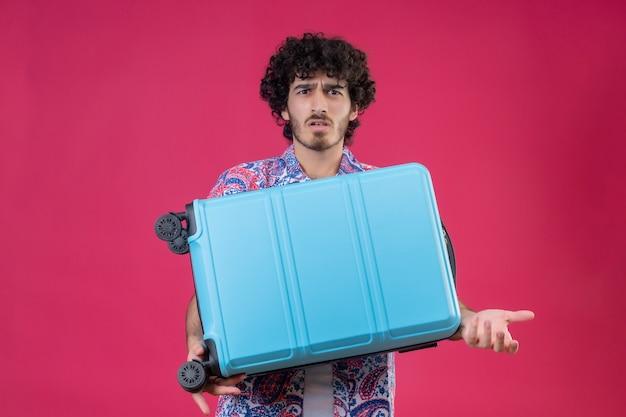 Verwirrter junger hübscher lockiger reisender mann, der koffer hält und leere hand auf lokalisiertem rosa raum mit kopienraum zeigt