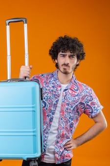 Verwirrter junger hübscher lockiger reisender mann, der koffer mit hand auf taille auf lokalisiertem orange raum hält