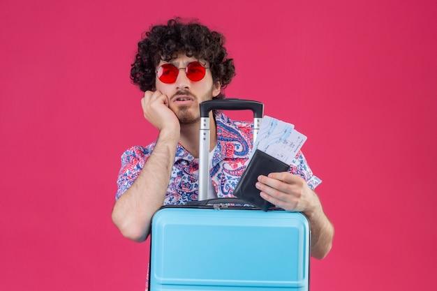 Verwirrter junger hübscher lockiger reisender mann, der sonnenbrille hält, die brieftasche und flugtickets hält, die hand auf wange mit koffer auf isoliertem rosa raum mit kopienraum setzen