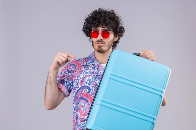 Verwirrter junger hübscher lockiger reisender mann, der sonnenbrille hält, koffer hält und auf ihn auf isoliertem weißem raum mit kopienraum zeigt