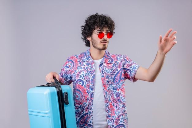 Verwirrter junger hübscher lockiger reisender mann, der sonnenbrille hält, koffer hält und hand auf der rechten seite auf isoliertem weißem raum ausstreckt