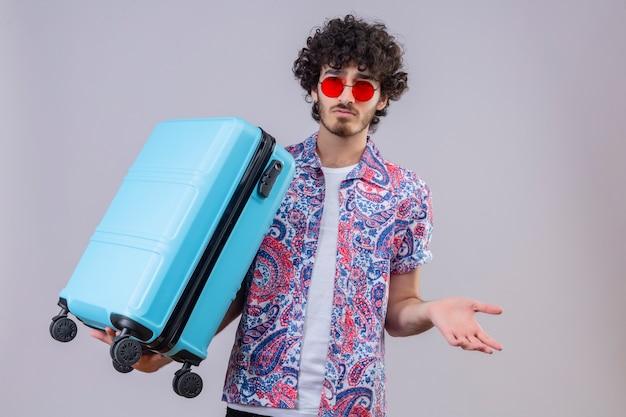 Verwirrter junger hübscher lockiger reisender mann, der sonnenbrille hält, koffer hält und leere hand auf lokalisiertem weißem raum mit kopienraum zeigt