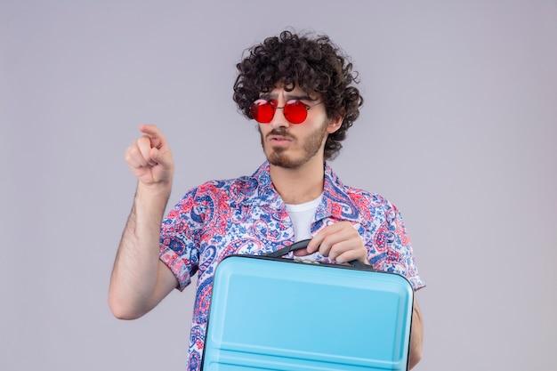 Verwirrter junger hübscher lockiger reisender mann, der sonnenbrille hält, koffer hält und vorne auf isolierten weißen raum mit kopienraum zeigt
