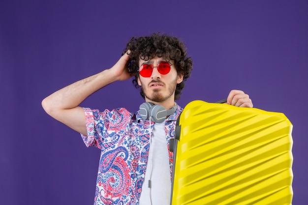 Verwirrter junger hübscher lockiger reisender mann, der sonnenbrille hält koffer mit hand auf kopf auf lokalisiertem lila raum hält