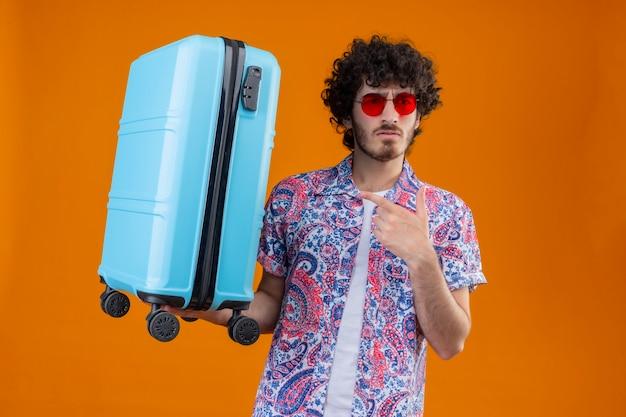 Verwirrter junger hübscher lockiger reisender mann, der sonnenbrille trägt und koffer hält, der auf ihn auf lokalisiertem orange raum mit kopienraum zeigt