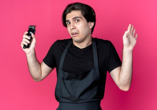 Verwirrter junger hübscher männlicher friseur in der uniform, die haarschneidemaschine hält und hand ausbreitet