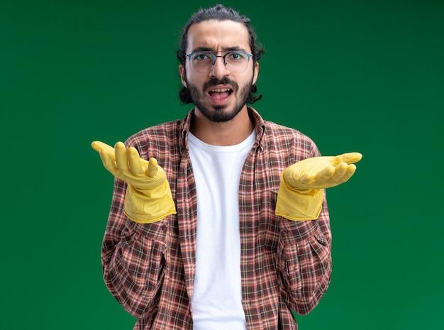 Verwirrter junger hübscher putzmann, der t-shirt und handschuhe trägt, die hände lokalisiert auf grüner wand verbreiten