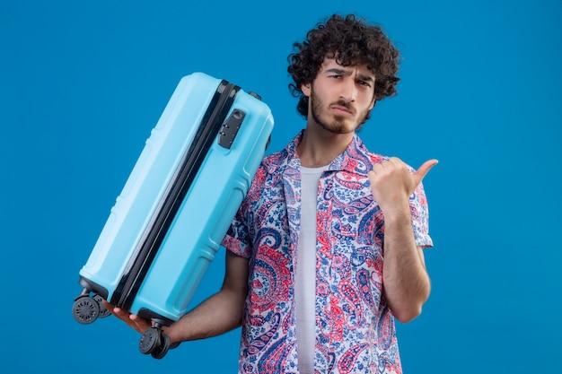 Verwirrter junger hübscher reisender mann, der koffer hält, der auf der rechten seite auf isoliertem blauem raum mit kopienraum zeigt