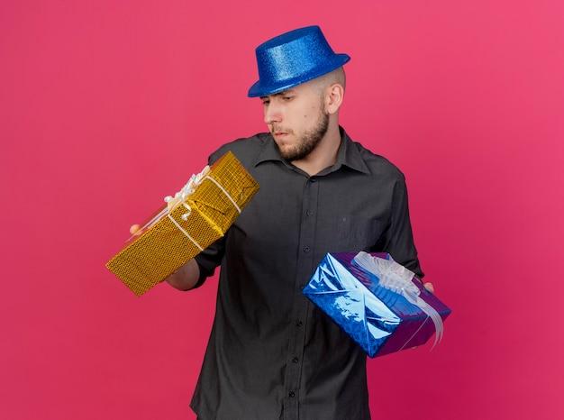 Verwirrter junger hübscher slawischer party-typ, der partyhut hält, der geschenkpackungen hält, die einen von ihnen lokalisiert auf purpurrotem hintergrund mit kopienraum betrachten