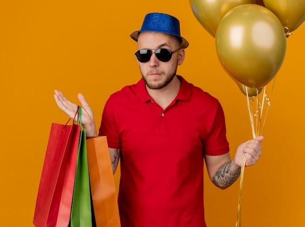 Verwirrter junger hübscher slawischer party-typ, der sonnenbrille und partyhut hält, der luftballons und papiertüten hält, die auf orange hintergrund lokalisiert werden